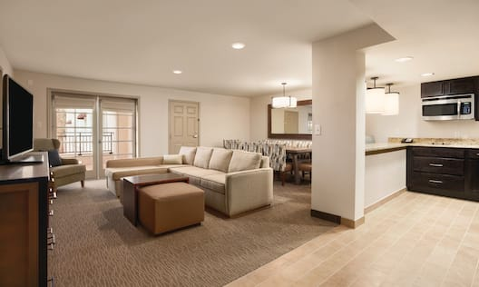 Suite Living Room Area With View of Entry, Wall Mirror, Dining Table With Seating for Six, Kitchen With Microwave, TV, Sofa, Ottoman, and Arm Chair in Corner by Balcony Doors