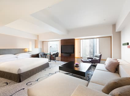 Guest Room with a Large Bed Table and Two Chairs HDTV and Sofa