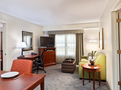 Suite Living Area With Dining Table, Work Desk, TV in Corner by Window With Sheer Drapes, Sofa, Lamp on Side Table and Open Doorways to Bedroom Areas