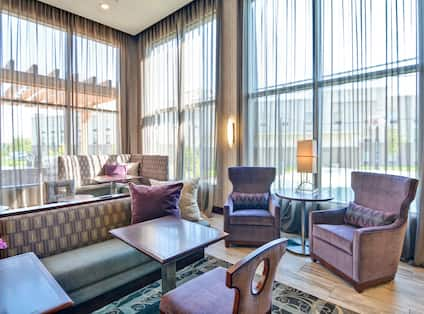 Lodge seating area with sofas, soft chairs, coffee tables, and floor-to-ceiling windows