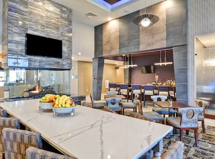 Lobby dining space with bar, dining tables, chairs, fireplace, and TV
