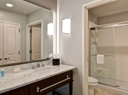 Suite bathroom with walk-in shower, toilet, vanity mirror, sink, and towels