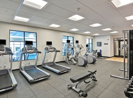 Fitness center with exercise machines, free weights, and windows