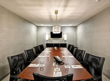 Executive boardroom with long table, chairs, and TV