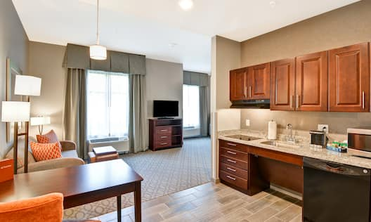Accessible studio suite with kitchen, dining tables, chairs, sofa, coffee table, ottoman, and TV