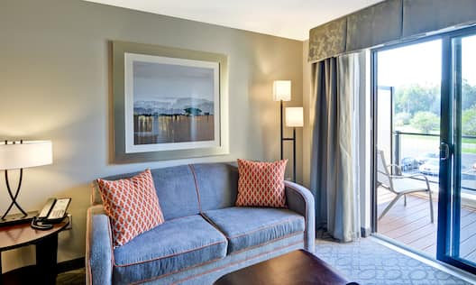 Suite living room with sofa, coffee table, lamps, and balcony patio door with outdoor view