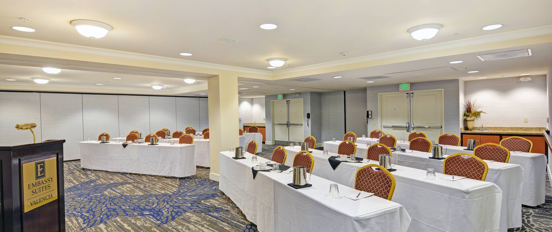Meeting room with classroom setup, cloth-covered tables, chairs, and speaking podium