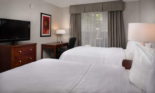Suite with two double beds, work desk, and TV