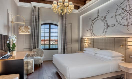 Guest Room with Large Bed HDTV and Windows with City View