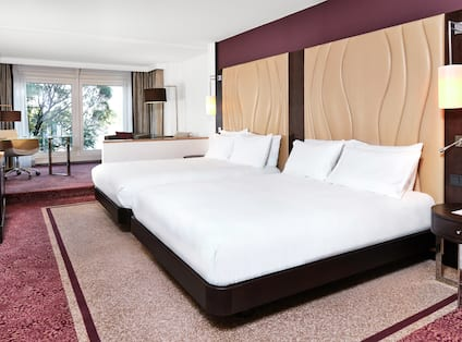 Junior Suite with Two Queen Beds and Tables with Lamps Beside Both Beds