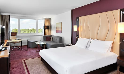 Hotel Room with One King Bed and a Waterfront View from Large Picture Frame Windows