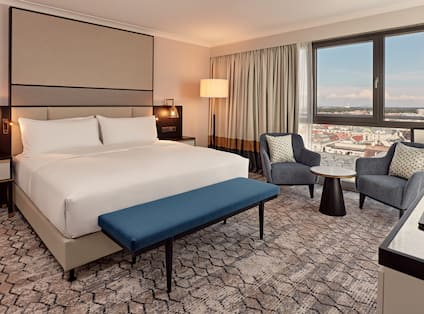 Large Bed in Room with Small Table and Two Armchairs Next to a Window Offering City View