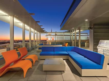 View of City From Illuminated Roof Top Terrace With Orange Chairs, Tables, Blue Sofa, and Grill at SunsetPanoramic City Views from the Rooftop Deck