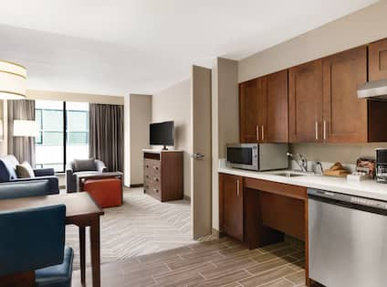 Kitchen and Living Areas in 2 Queen Bed 1 Bedroom Suite with Dining Tables, Microwave, Dishwasher, sink, Coffee Maker, Sofa, Arm Chair, TV, and Outside ViewKing Suite with Full Kitchens with Flexible Dining Areas and Separate Lounge Areas