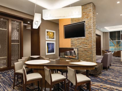 TV and Bar Table Seating by Fireplace in Lodge Area With Additional Soft Seating in BackgroundSeating Area with HDTV, Elegant Lighting and a Gas Fireplace
