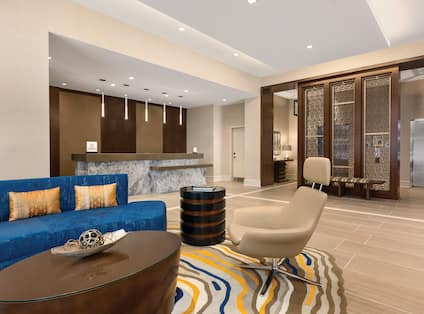 Sofa, Tables, and Arm Chair Seating in Lobby With View of Front DeskLobby Featuring Seating Areas, Concierge Desk and Elegant Décor
