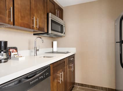 Kitchen With Dishwasher, Coffee Maker, Sink, Microwave Over Stove Top, and Fridge In-Suite Kitchen with a Dishwasher, Microwave, Full-Size Refrigerator, Stovetop and Sink
