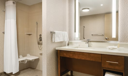 Roll-in Shower with Bench, Grab Bars, Handheld Showerhead and Vanity Mirror, Sink, Towels, and Toiletries in Accessible BathroomAccessible Bathroom with a Walk-In Shower, Seat and a Removable Shower Nozzle