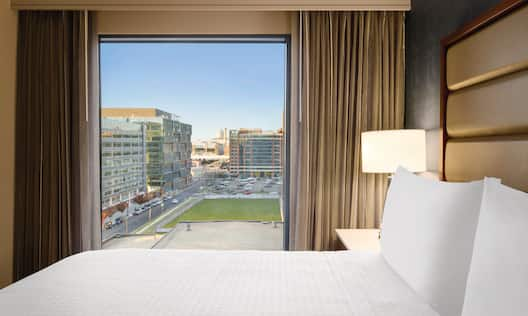 King Bed and Bedside Table with Lamp by Window with Open DrapesKing Mattress Beside a Window with Stunning City Views