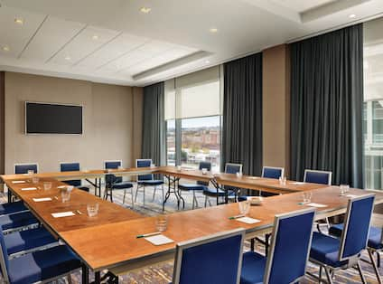 Square Boardroom-Style Setup With Seating for 16, TV in Meeting Room With Large WindowsMeeting Space in the Conference-Style Setup with Office Chairs and Mounted TV