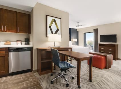 Kitchen With Sink, Dishwasher, Coffee Maker, Wall Art, Work Desk and View of Bed, Ceiling Fan, Window and TV in Bedroom Area of Studio SuiteFlexible Dining and Work Desks with Ergonomic Chairs