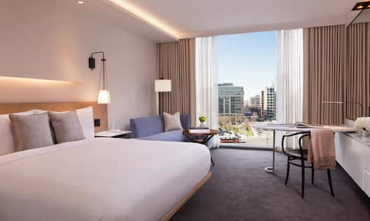 Deluxe King Guestroom with Bed, Lounge Area, Work Desk, and Outside View