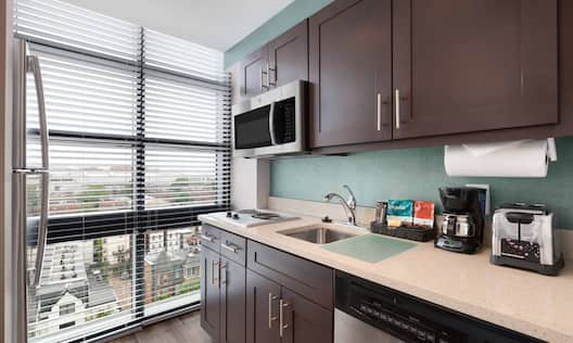 Fridge by Large Window, Microwave Over Stovetop, Sink, Coffee Maker, Toaster, and Dishwasher in Kitchen of King Suite