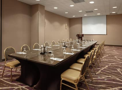 Embassy Suites Potomac Meeting Room with Table, Chairs, and Projector Screen