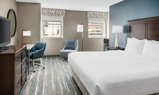 Bed in room with TV and chairs
