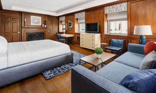 Bed in room with comfortable seating and TV