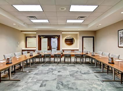 Meeting Room in Classroom Style With Decorated Long Tables and Chairs Facing Podium