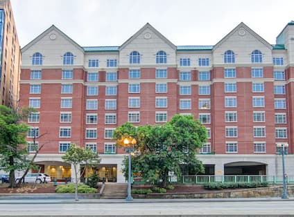Daytime View of Hotel Exterior, Signage, and Landscaping, With Guest Cars in Front