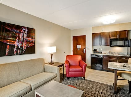 Living Room With Soft seating and Wall Art by Suite Entry With Kitchen Area in Background