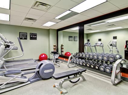Fitness Center with Large Windows, Cardio Equipment, TV, and Full Length Mirror