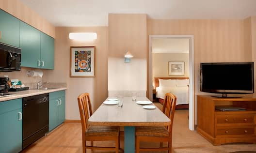 In-suite Kitchen With Microwave Over Stovetop, Coffee Maker, Dishwasher, Sink, Wall Art, Dining Table, and Open Doorway by TV to Bedroom
