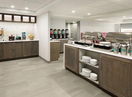 Breakfast serving area with buffet trays, coffee, juice, cereals, oatmeal, fruits, and dining amenities