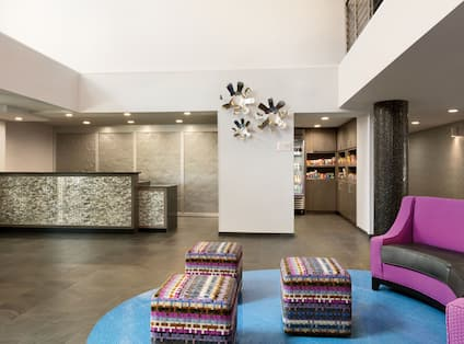 Lobby front desk with seating area curved sofa, and ottomans