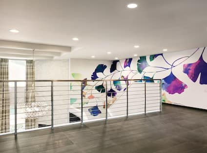 Lobby upper floor with view of descending staircase and mural wall art