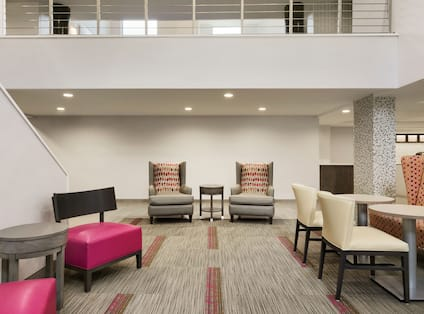 Lobby atrium seating area with soft chairs, lavish sofas, small tables, and view of second floor banister