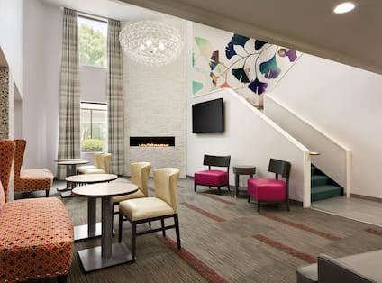 Lobby atrium seating area with soft chairs, lavish sofas, small tables, TV, ascending staircase, fireplace, and window with outdoor view
