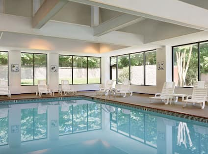 Indoor pool with lounge chairs and windows with outdoor view