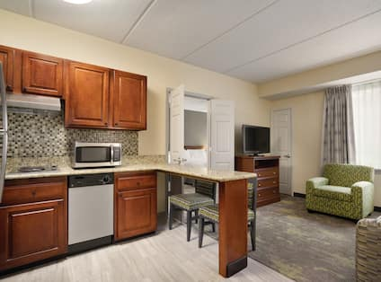 Kitchen and Loving Areas in Mobility King Suite With Open Doorway to Bedroom