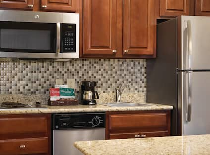 Kitchen With Microwave Over Stove Top, Dishwasher, Coffee Maker, Sink and Fridge