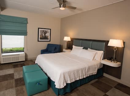 Suite king bed with nightstands, lamps, soft chair, and ottoman