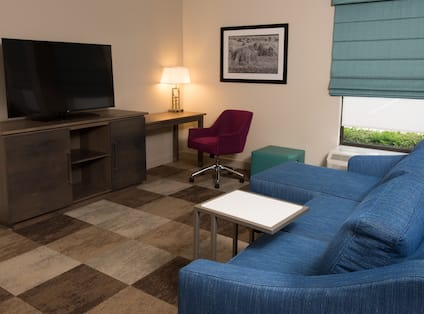 Suite living area with L-shaped lounge sofa, ottoman, work desk, and TV