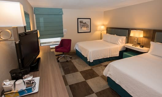 Accessible guestroom with two queen beds, nightstand, lamps, work desk, and TV