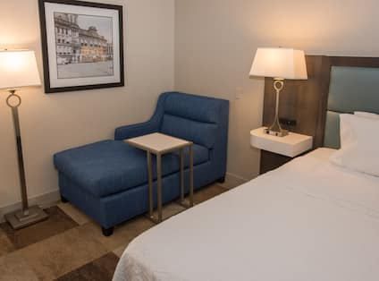 King bed with nightstand, floor lamp, and chaise lounge chair