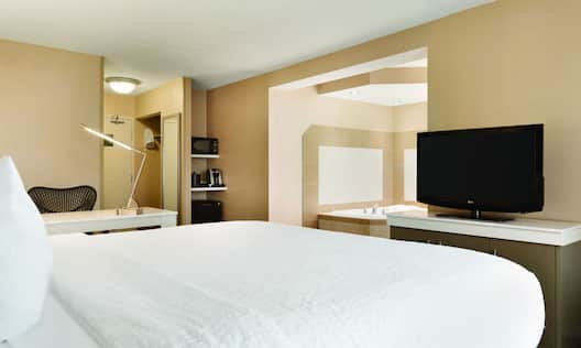 King Bed, Work Desk, Entry Hospitality Center With Microwave, Kuerig, and Mini Fridge, Open Doorway to View of Whirl Pool,  and TV in  Guest Room