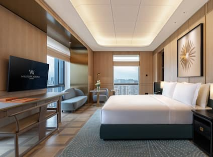 Guest Room with Large Bed Sofa HDTV and City View