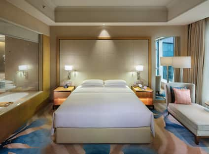 King guest room with king bed, lounge chair, and transparent window with view into bathroom
